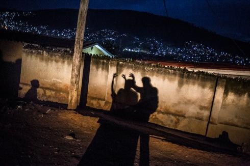 13 décembre 2016, Kigali, RWANDA. Jouer aux ombres chinoises avec les phares d'une voiture et des enfants dans le quartier populaire de Nyamirambo à Kigali à la tombée de la nuit.