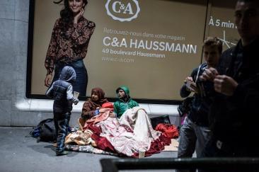 """19 octobre 2016, Paris, France. Les jeunes de Génération Identitaire Paris collent des stickets """"Chassons les islamistes"""" devant des migrants sur le boulevard Haussmann. Les migrants ne comprennent pas ce qu'il y a marqué. Ils prennent cela pour un jeu et veulent les aider."""