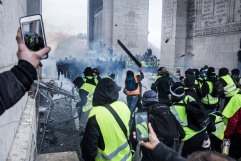 December 1st, 2018, Paris (75), FRANCE. Demonstrators, known as yellow jackets, attack policemen trying to hold position under the Arch of Triumph in Paris. They will manage to erect a barricade for a few moment under the arch of Triumph. Demonstrations were held everywhere in France. People from low class started to ask the government to give up on new gas taxes. Their claims being ignored they tend to ask for tax justice and more purchasing power.